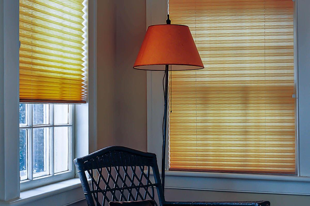 In this guest bedroom, yellow pleated shades light soft light filter through.