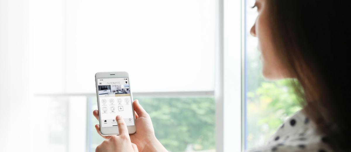 A woman holds her mobile phone, using the hub app, with windows with roller shades in the background