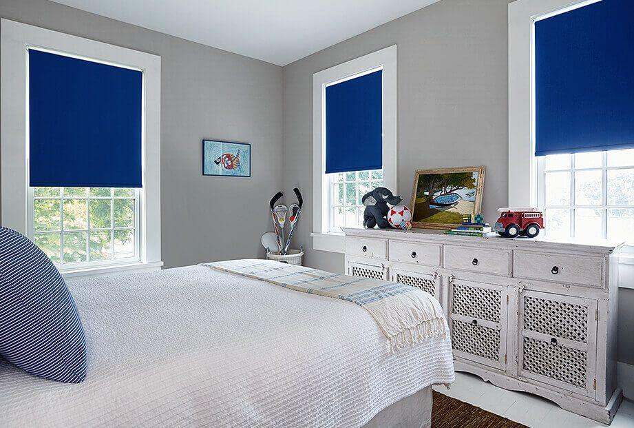 Blue roller shades matching the rest of the decor in this bedroom.