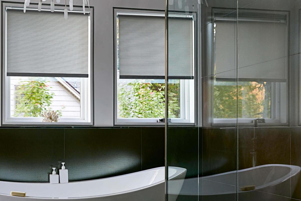 This bathroom has dark grey roller shades which gives privacy while letting soft light filter through the windows