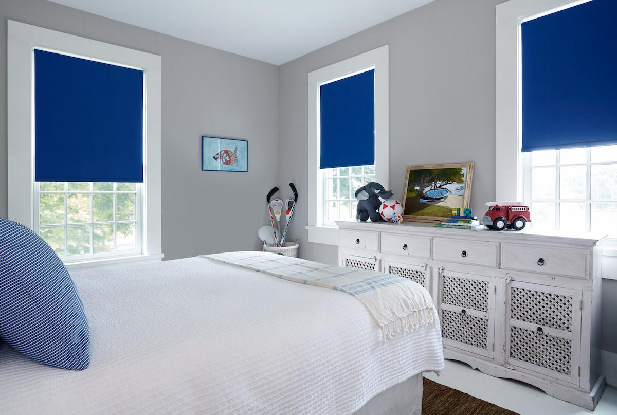 Blue roller shades with blackout lining in a child's bedroom