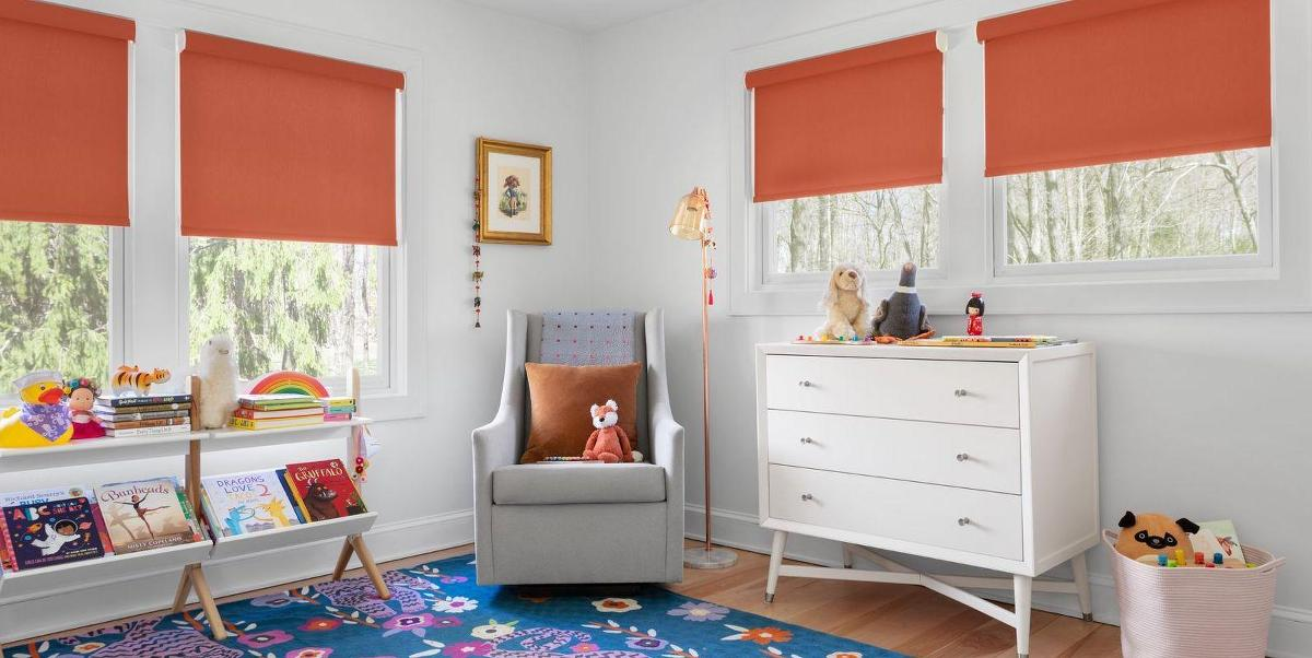 Roller shades in a playful orange color brighten up a whimsical children's room
