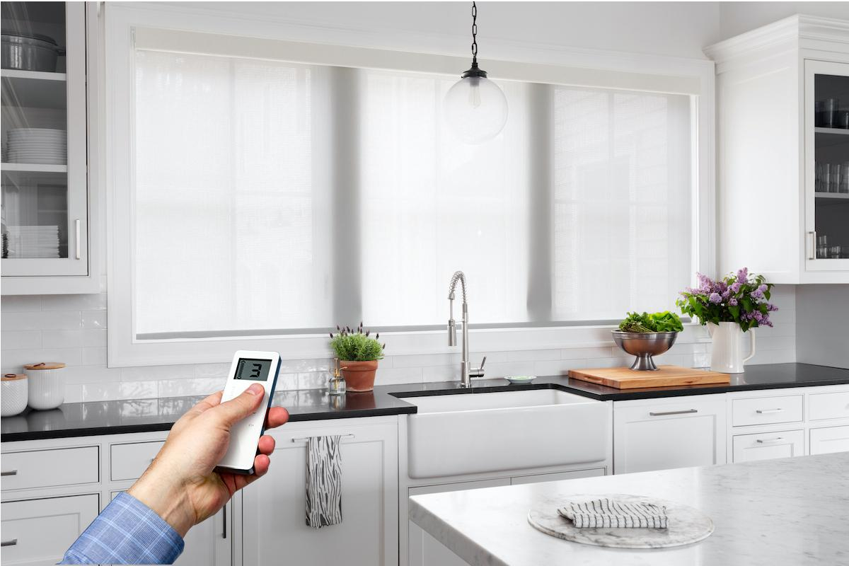 White solar shades allow light and partial view from a large window in a contemporary kitchen, with a hand holding a remote in the foreground