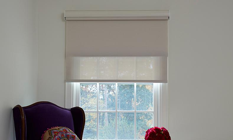 Side by side images of a window in a living room, show that you can pull down the sheer or blackout shades independently of one another with a double roller shade.