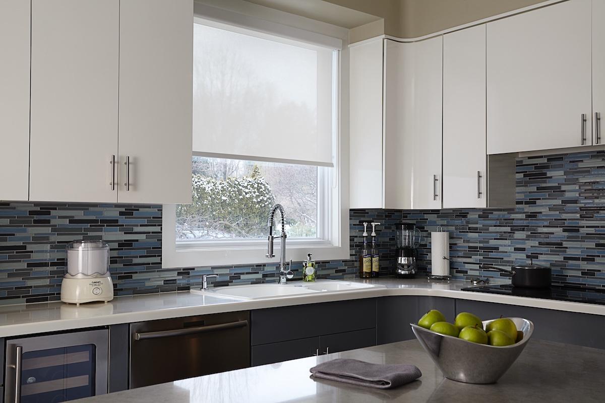 Une fenêtre de cuisine ornée d'une toile solaire blanche