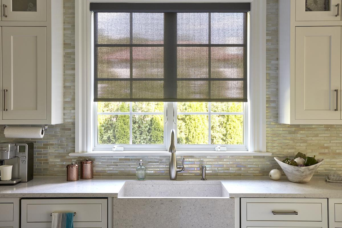 Taupe colored solar shades allow in light and partial view over a modern farmhouse-style sink in a contemporary kitchen
