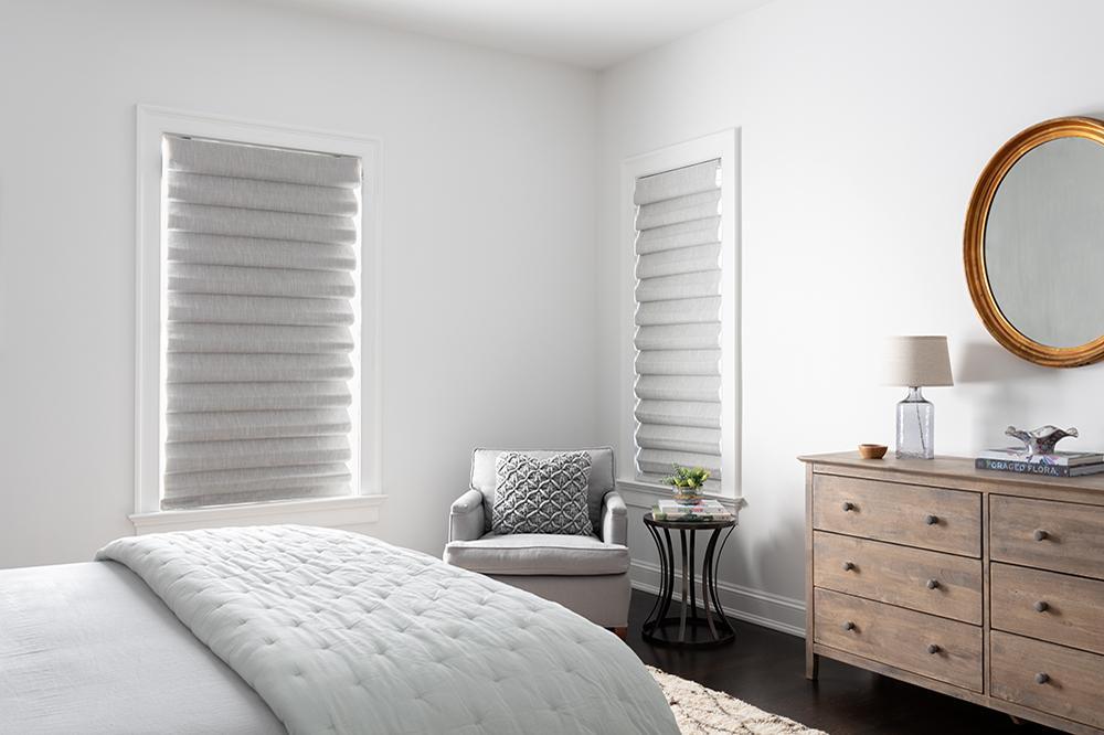 Des stores romains gris clair aux plis classiques dans une chambre à coucher moderne