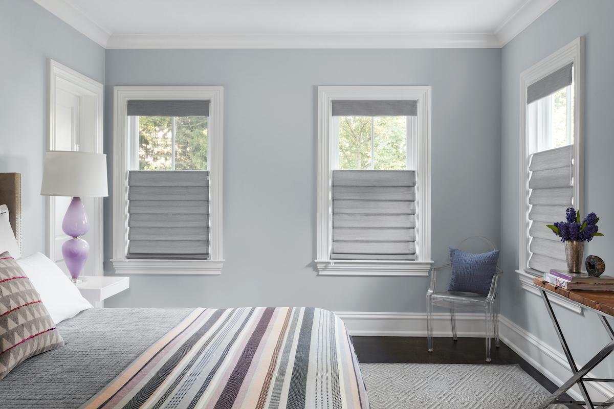 Roman shades with top-down bottom-up feature let light in from the top of the window treatments in a contemporary bedroom
