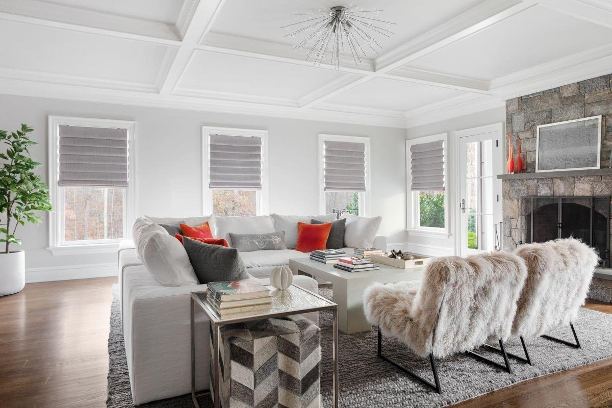 Grey roman shades with classic pleating cover four windows in a contemporary living room.