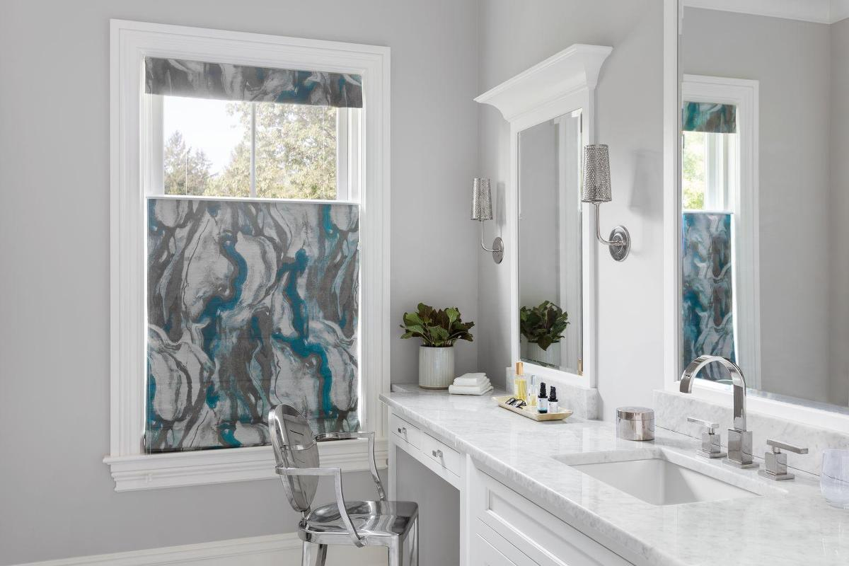 A blue and grey marbled fabric roman shade adds beauty and interest to a bathroom vanity window, the top is down allowing light in but providing privacy