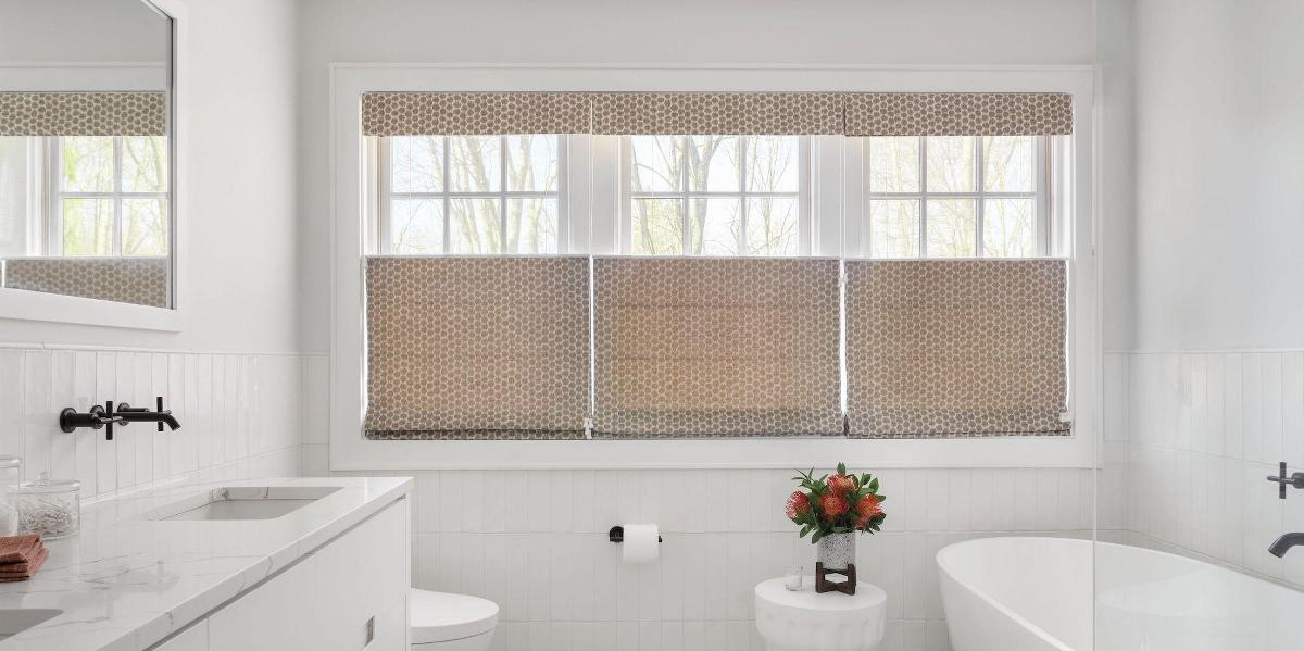 Three side-by-side windows showcase tan roman shades with the top lowered to let light in