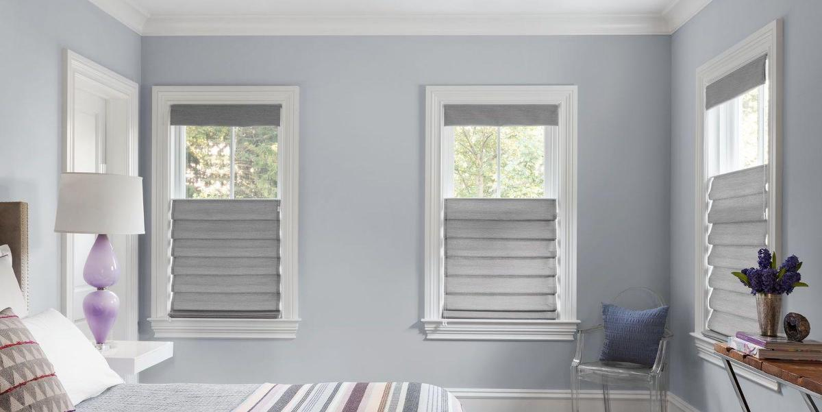 Top-down bottom-up roman shades are open on the top but not the bottom in a contemporary bedroom