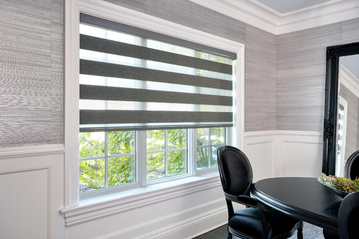 A grey and white dining room with a large window features a grey Cascade Sheer Shade halfway down in the open position