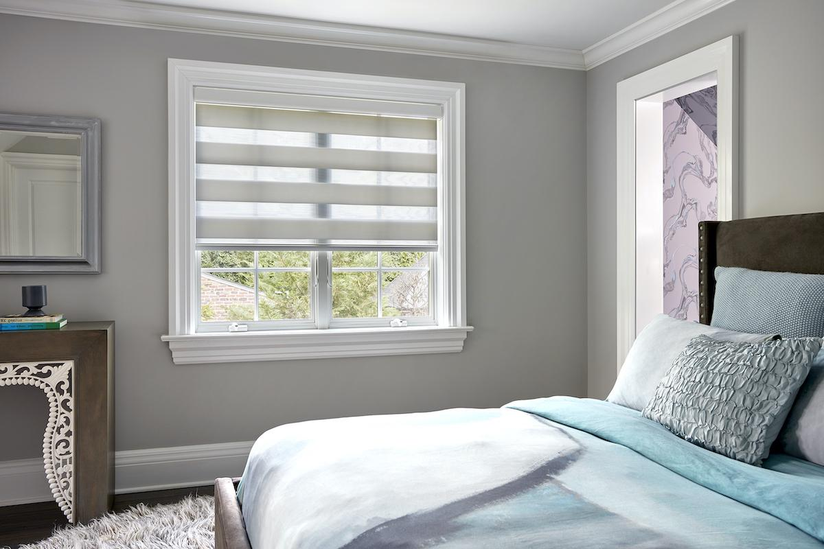 The window in a grey-colored bedroom features a white Cascade shade in halfway down position, allowing partial view of the outside