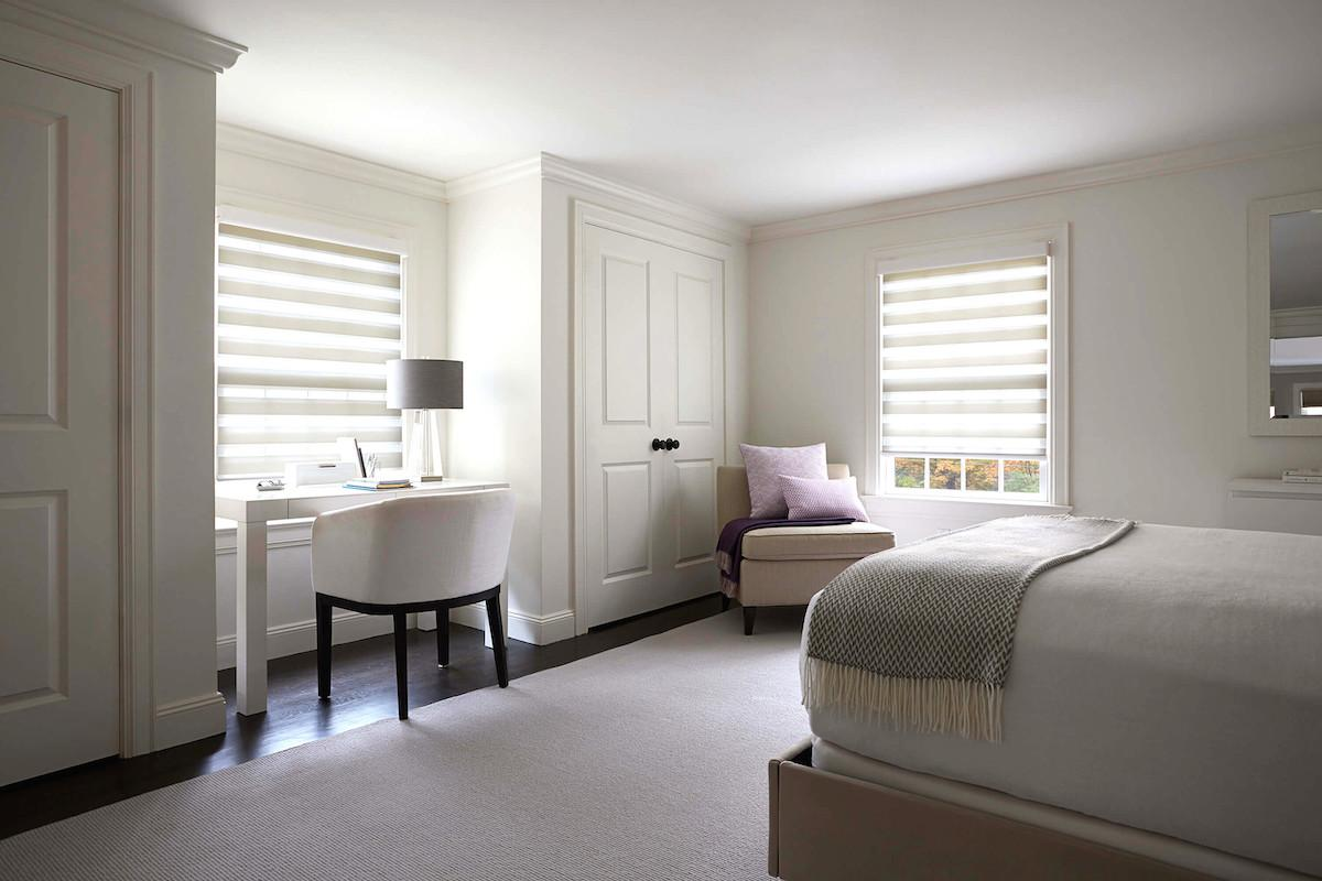 Light shines through two windows, that are covered with white Cascade sheer shades in a contemporary bedroom