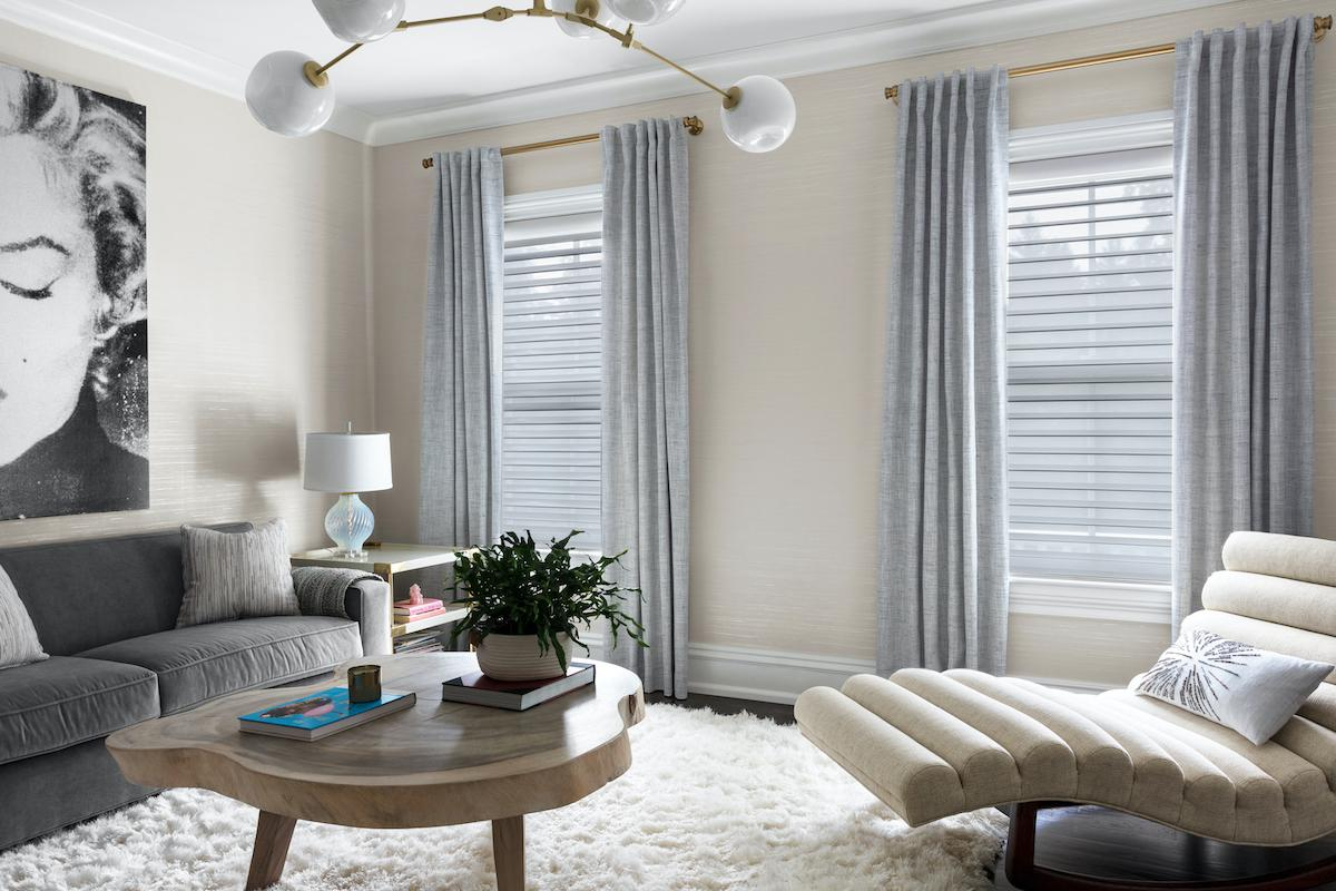 A bright living area with light grey tones features a Serenity sheer shade in light grey on the window