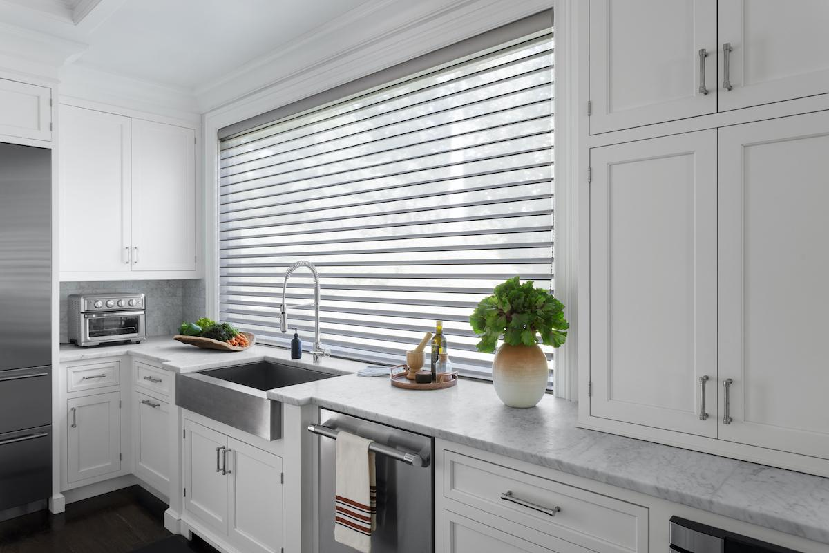 A contemporary kitchen features white Serenity sheer shades on three windows