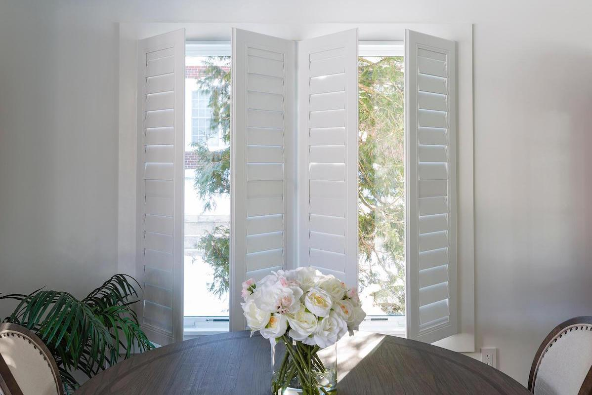 White indoor shutters, ajar in a small contemporary dining room, allow light to pour into the room