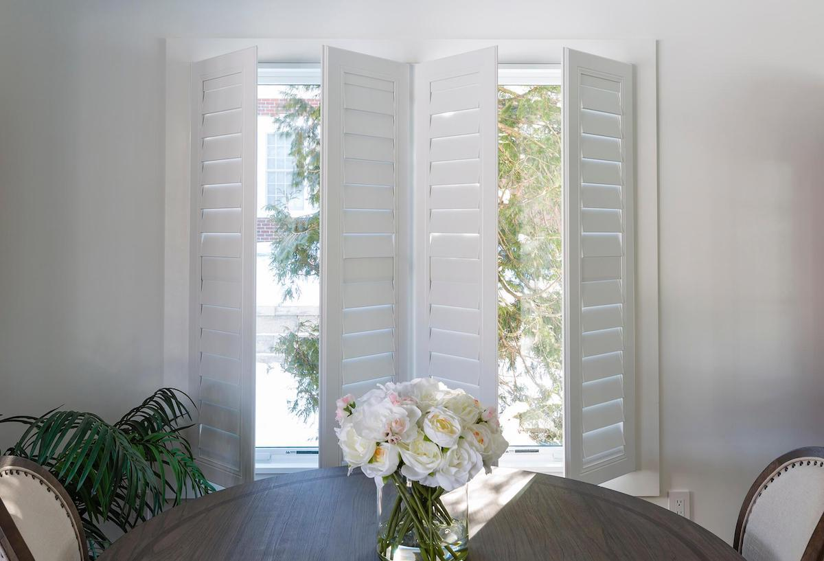 White indoor shutters open into a small, bright dining room