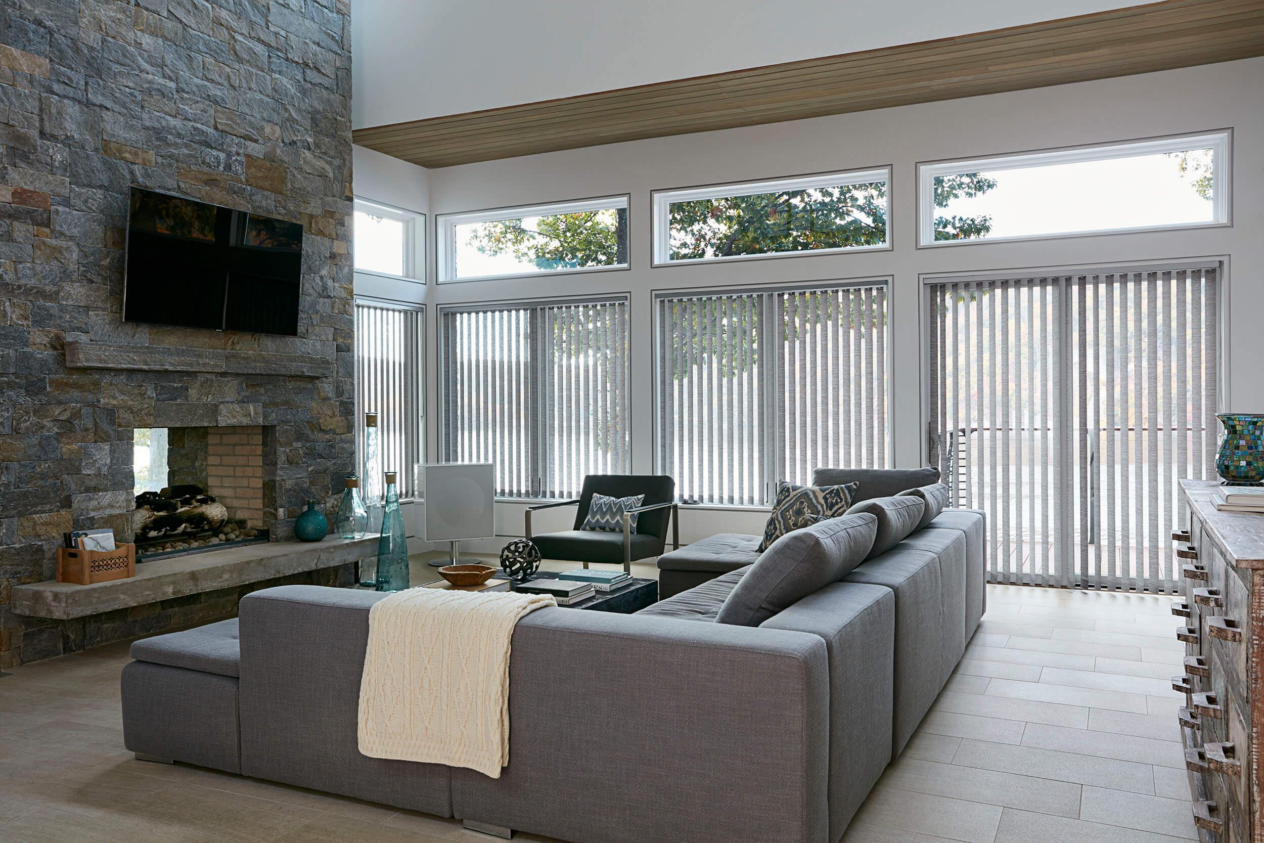 Stores verticaux faits avec un tissu texturé beige et brun dans une salle familiale aux hautes fenêtres avoisinantes.
