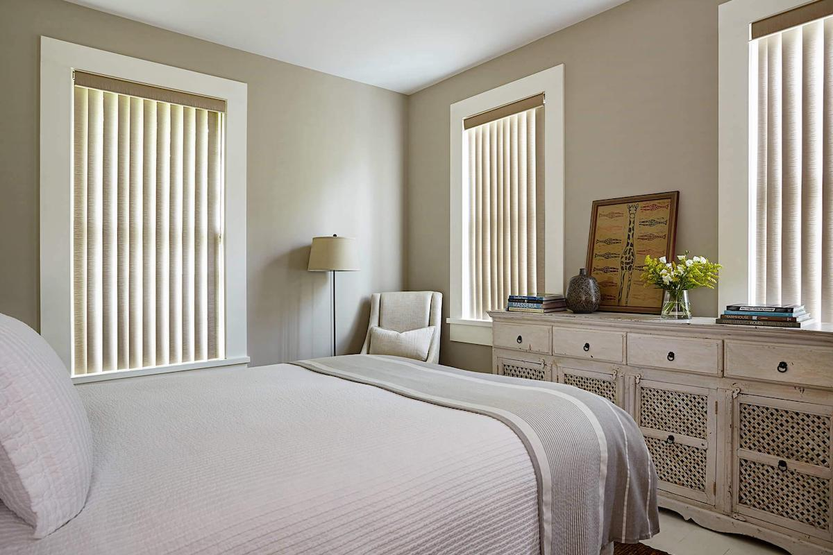 Tan vertical blinds in a contemporary bedroom