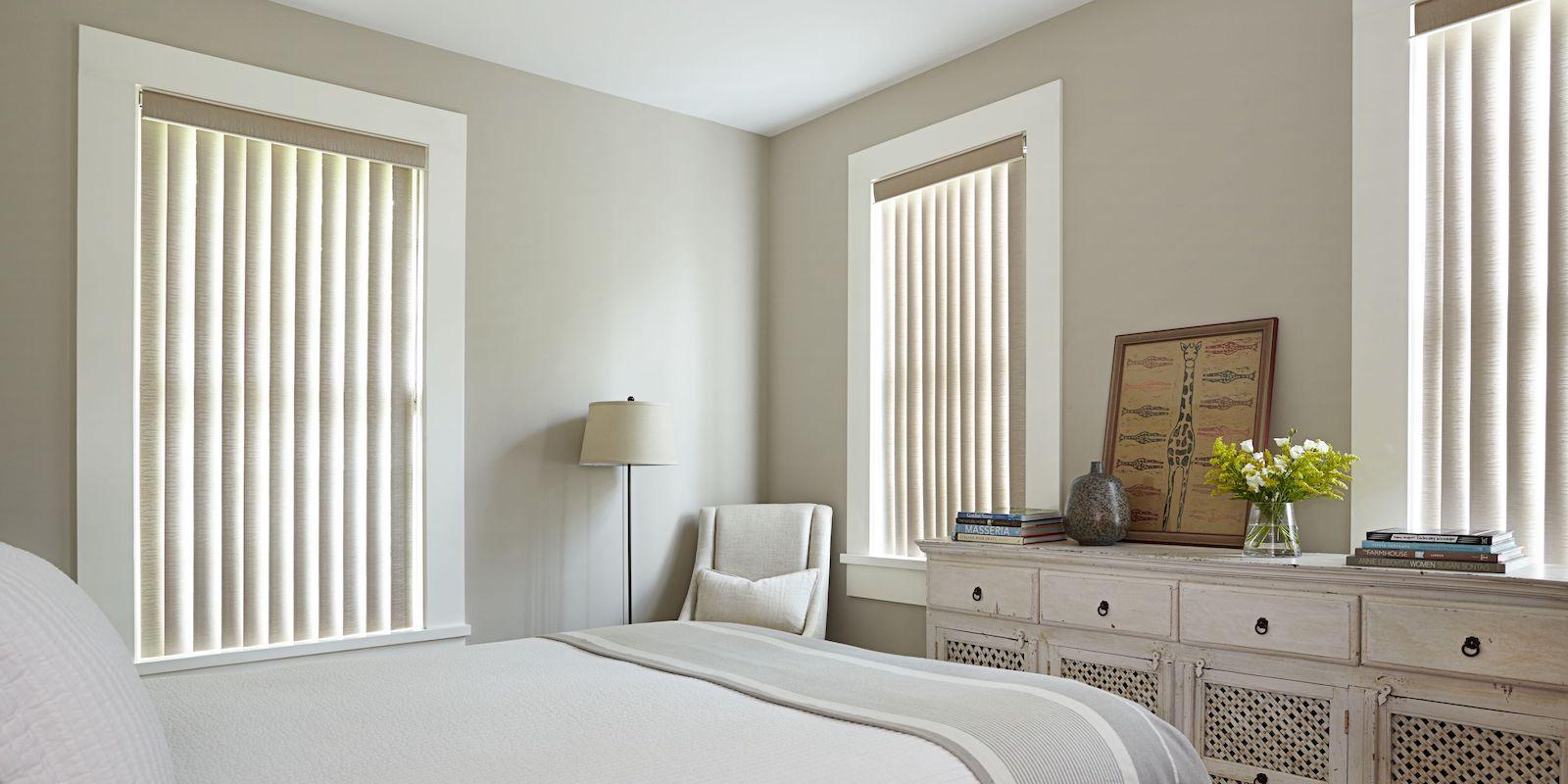 Stores verticaux de ton beige dans une chambre à coucher au cachet contemporain.