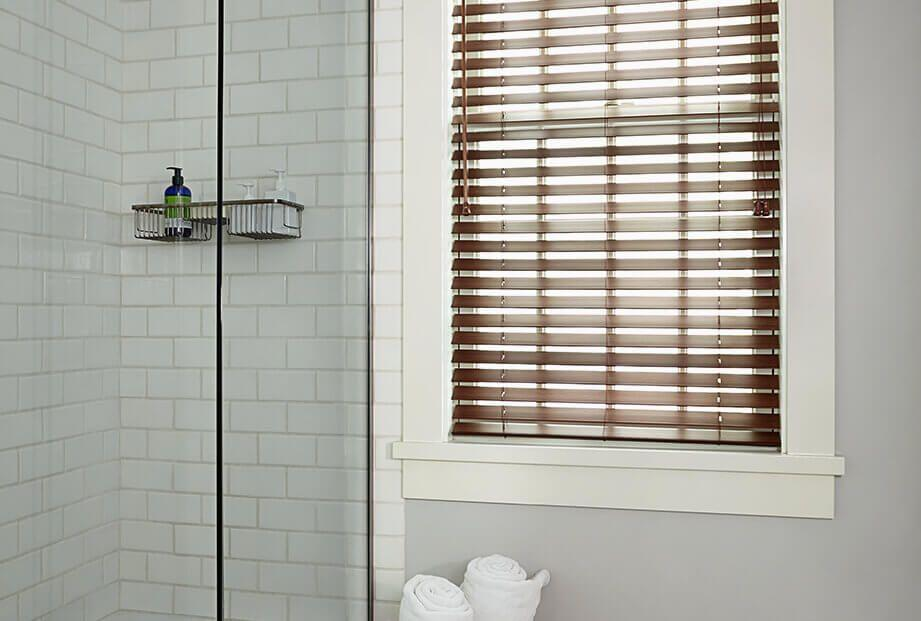 Faux wood blinds in a bathroom setting, perfect for moist rooms.