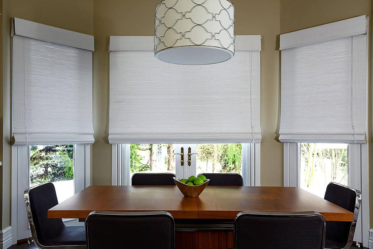 This elegant dining room has it's window covered by simple white woven wood shades