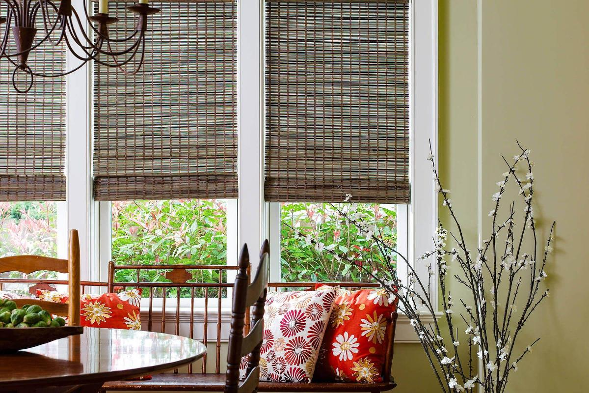 Dark brown woven wood shades help complete this breakfast nook. A simple yet elegant window treatment designed by Blinds To Go