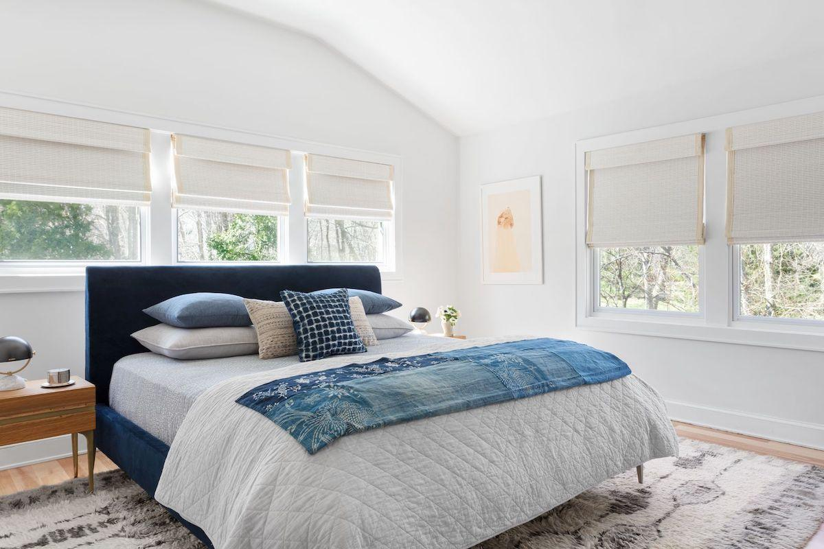 White woven wood shades with blackout lining cover 5 windows in a contemporary bedroom