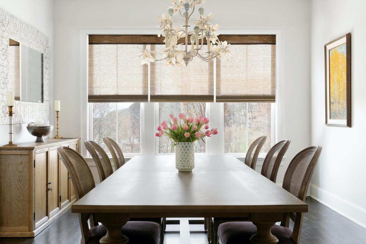 An elegant dining room with 3 large, side-by-side windows features three woven wood shades on a shared headrail