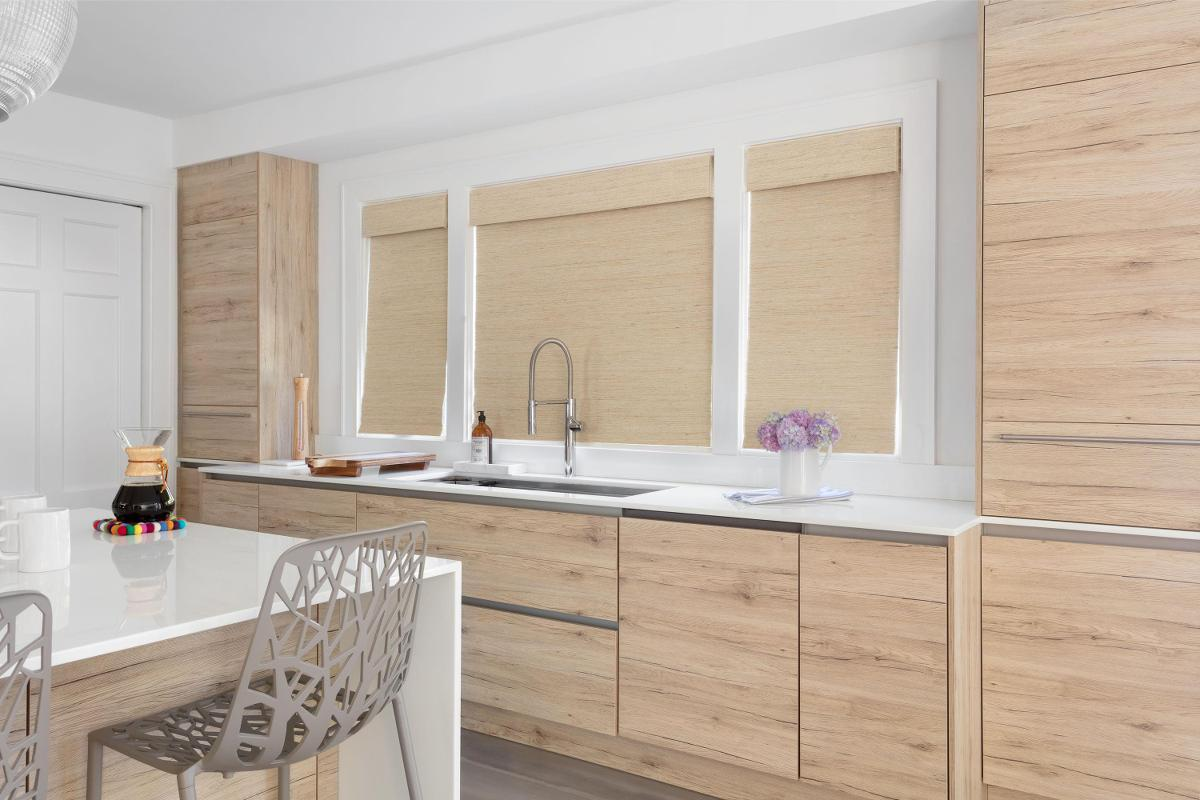 Woven wood shades in a light wood tone match the cabinets in a modern kitchen