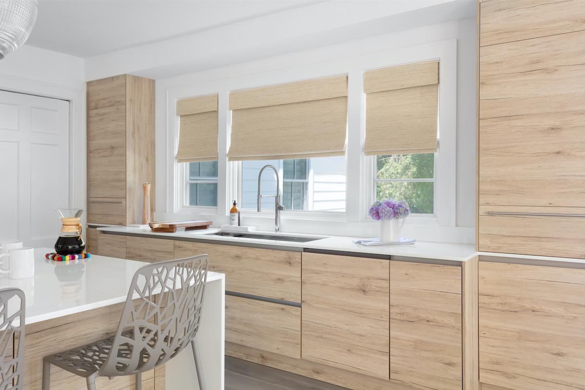 A modern kitchen with bamboo cabinets features woven wood shades in a similar tone on the three windows over the sink