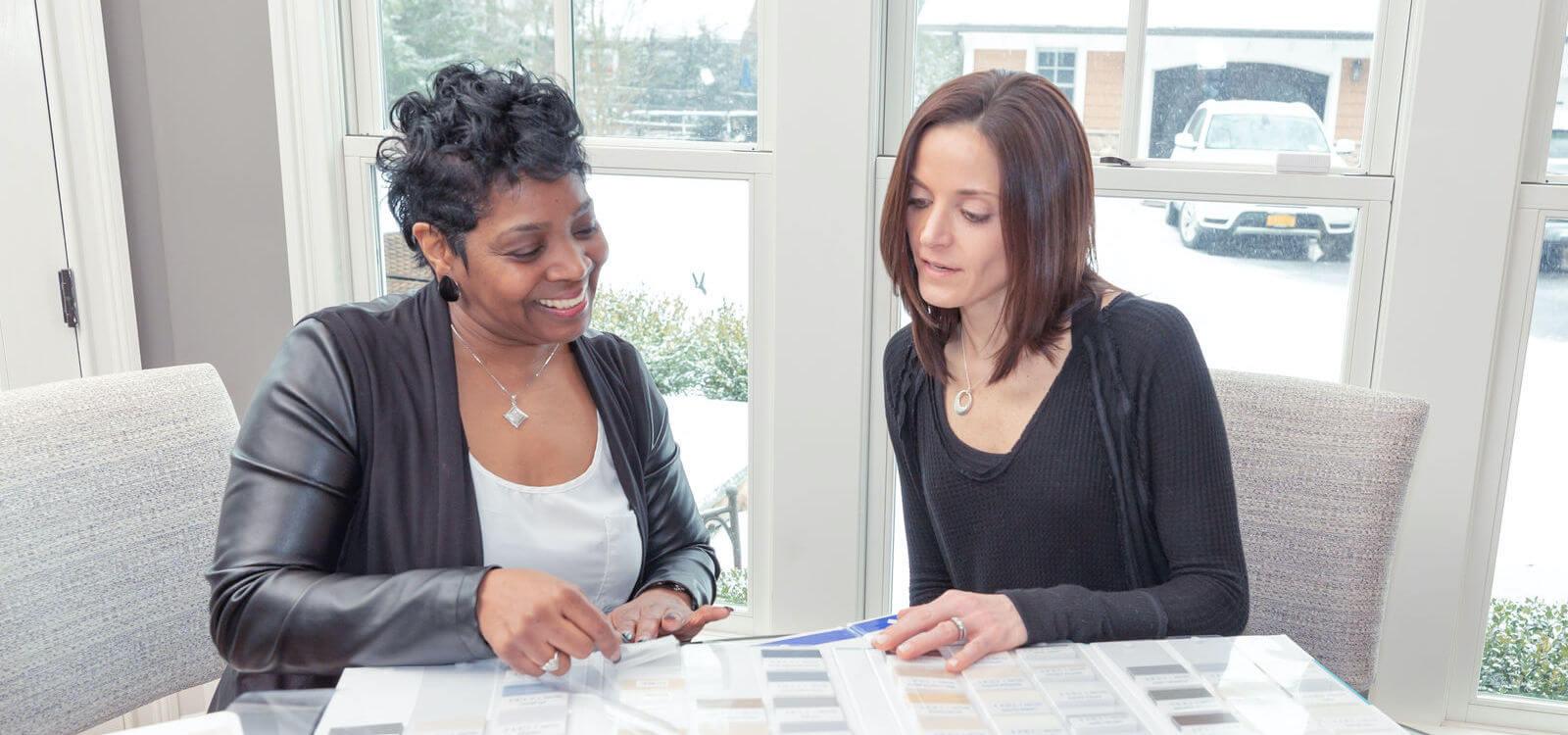 Une conseillère en décoration du Service à domicile montre des échantillons à une femme assise à une table de salle à dîner.